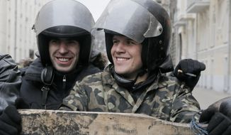 Protesters smile as they guard the entrance to Ukrainian President Yanukovych's office in Kiev Ukraine, Saturday, Feb, 22, 2014. Ukrainian security  and volunteers from among Independence Square protesters have joined forces to protect the presidential office  from vandalism and marauding. Yanukovych left Kiev for his support base in the country's Russian-speaking east, but an aide said that he has no intention of abandoning power.(AP Photo/Efrem Lukatsky)