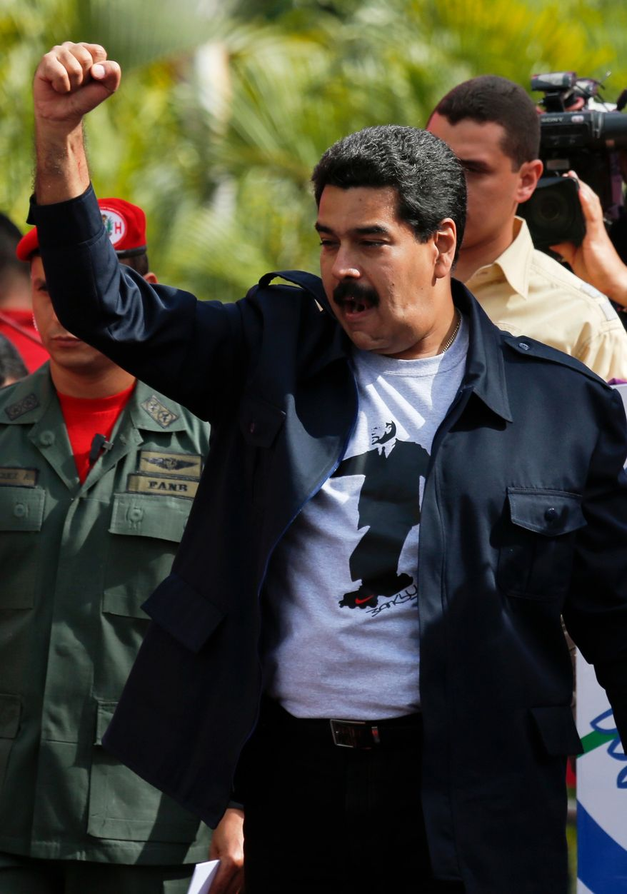 Venezuela's President Nicolas Maduro greets supporters upon his arrival for a rally outside Miraflores Presidential Palace in Caracas, Venezuela, Saturday, Feb. 22, 2014. Venezuelans on both sides of the nation's political divide took to the streets on Saturday after nearly two weeks of mass protests that have Maduro scrambling to reassert his leadership of his bitterly divided country. (AP Photo/Fernando Llano)