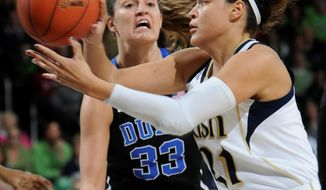 Notre Dame guard Kayla McBride, right, throws a pass around Duke forward Haley Peters during first half action in an NCAA women's college basketball game, Sunday, Feb. 23, 2014, in South Bend, Ind. (AP Photo/Joe Raymond)