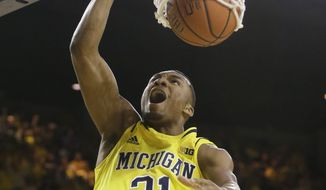 Michigan guard Zak Irvin (21) dunks during the first half of an NCAA college basketball game against Michigan State in Ann Arbor, Mich., Sunday, Feb. 23, 2014. (AP Photo/Carlos Osorio)
