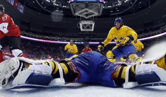 Canada forward Sidney Crosby scores a goal on Sweden goaltender Henrik Lundqvist during the second period of the men's gold medal ice hockey game at the 2014 Winter Olympics, Sunday, Feb. 23, 2014, in Sochi, Russia. (AP Photo/Julio Cortez, Pool)