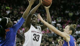 South Carolina's Elam Ibiam (33) takes attempts a shot as Florida's Jaterra Bonds and Lily Svete, right, defend during the first half of their NCAA women's college basketball game, Sunday, Feb. 23, 2014, in Columbia, S.C. (AP Photo/Mary Ann Chastain)