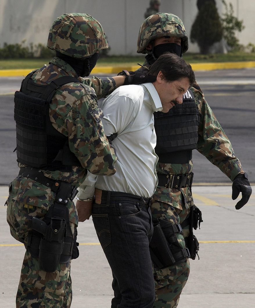 """Joaquin """"El Chapo"""" Guzman is escorted to a helicopter in handcuffs by Mexican navy marines at a navy hanger in Mexico City, Mexico, Saturday, Feb. 22, 2014. After 13 years on the run, narrow escapes from the military, law enforcement and rivals, Guzman is back in Mexican custody. Now starts what is likely to be a lengthy and complicated legal process to decide which country gets to try him first.  (AP Photo/Dario Lopez-Mills)"""