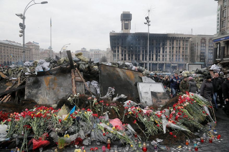 Associated Press photographsFlowers cover a barricade heading to Kiev's Independence Square, the epicenter of Ukraine's recent unrest on a day of mourning. Official reports say 82 people were killed in clashes between activists and riot police.