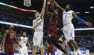 Temple guard Quenton Decosey (25) goes to the basket between Memphis forwards Austin Nichols (4) and Shaq Goodwin (2) in the first half of an NCAA college basketball game Saturday, Feb. 22, 2014, in Memphis, Tenn. (AP Photo/Lance Murphey)