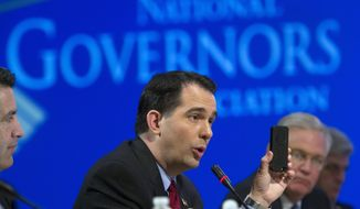 Wisconsin Gov. Scott Walker uses a cell phone to illustrate a point about health care plans during a special session on jobs in America during the National Governor's Association Winter Meeting in Washington, Sunday, Feb. 23, 2014. (AP Photo/Cliff Owen)