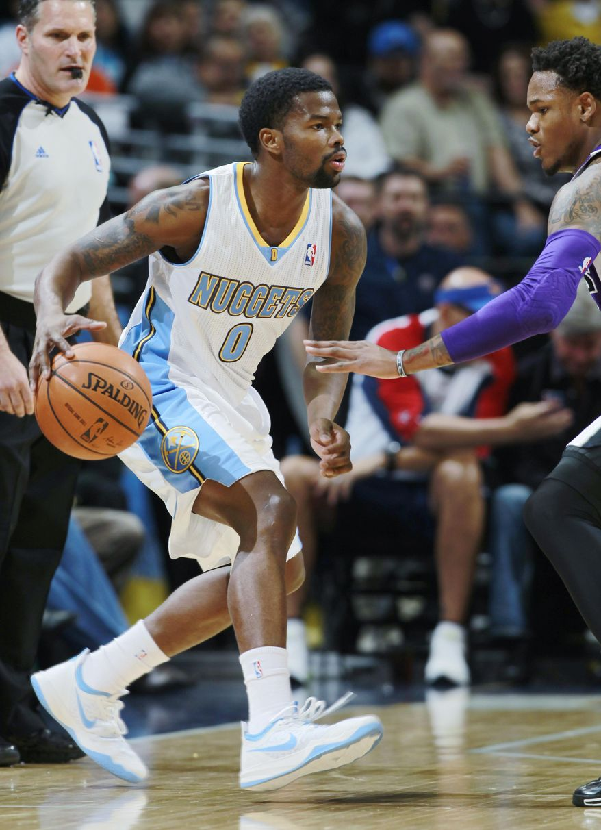 Denver Nuggets guard Aaron Brooks, left,  dibbles the ball as Sacramento Kings guard Ben McLemore covers in the first quarter of an NBA basketball game in Denver, Sunday, Feb. 23, 2014. (AP Photo/David Zalubowski)