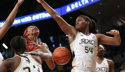 Maryland center Alicia DeVaughn (13) looses the ball as she tries to drive between Georgia Tech guard Sydney Wallace (23) and Georgia Tech forward Roddreka Rogers (54)in the second half of an NCAA college basketball game, Sunday, Feb. 23, 2014, in Atlanta. (AP Photo/John Bazemore)