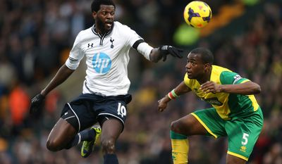 Norwich City's Sebastien Bassong, right, and Tottenham Hotspur's Emmanuel Adebayor compete for the ball during their English Premier League soccer match at Carrow Road, Norwich, England, Sunday, Feb. 23, 2014. (AP Photo/Stephen Pond, PA Wire)    UNITED KINGDOM OUT   -  NO SALES   -   NO ARCHIVES