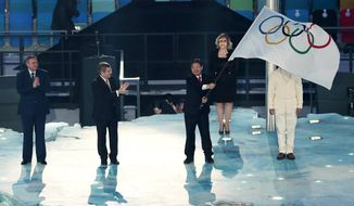 Mayor of Sochi Anatoly Pakhomov, left, and International Olympic Committee President Thomas Bach, second from left, applaud as Lee Seok-rai, mayor of Pyeongchang, waves the Olympic flag during the closing ceremony of the 2014 Winter Olympics, Sunday, Feb. 23, 2014, in Sochi, Russia. (AP Photo/Ivan Sekretarev)
