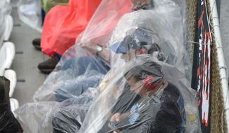 Race fans take cover from the rain in the stands during the NASCAR Daytona 500 auto race at Daytona International Speedway, Sunday, Feb. 23, 2014, in Daytona Beach, Fla. (AP Photo/Phelan M. Ebenhack)