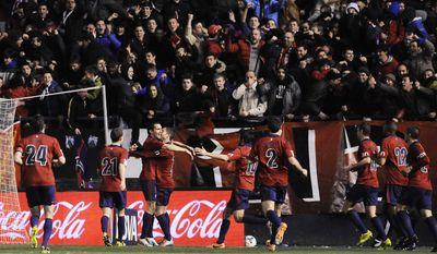 Osasuna's  Alvaro Cejudo, third from left,  celebrates his goal after scoring against Atletico de Madrid, during their Spanish League soccer match, at El Sadar stadium in Pamplona, Spain, Sunday, Feb. 23, 2014. (AP Photo/Alvaro Barrientos)