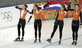Athletes from the Netherlands, left to right, Ireen Wust, Marrit Leenstra, Lotte van Beek and Jorien ter Mors hold their national flag and celebrate their gold in the women's team pursuit at the Adler Arena Skating Center at the 2014 Winter Olympics, Saturday, Feb. 22, 2014, in Sochi, Russia. (AP Photo/Matt Dunham)