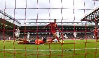 Liverpool's Jordan Henderson, centre, scores past Swansea City goalkeeper Michel Vorm, bottom left, during their English Premier League soccer match at Anfield Stadium, Liverpool, England, Sunday Feb. 23, 2014. (AP Photo/Jon Super)