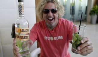 "In this Saturday, Feb. 22, 2014 photo, musician Sammy Hagar holds a bottle of his Beach Bar Rum, and a mojito made with the rum, during an interview in Miami. Hagar, known as the ""Red Rocker"" and lead singer of the band Van Halen, sold his part of the Cabo Wabo Tequila company not long ago and turned his attention to rum. Sammy's Beach Bar Rum is made in Hawaii, where Hagar has a home. (AP Photo/Lynne Sladky)"