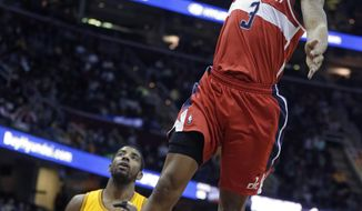Washington Wizards' Bradley Beal (3) dunks over Cleveland Cavaliers' Kyrie Irving (2) in the first quarter of an NBA basketball game, Sunday, Feb. 23, 2014, in Cleveland. (AP Photo/Mark Duncan)