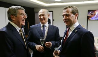 Russian President Vladimir Putin, center, talks with Prime Minister Dmitry Medvedev, right, and International Olympic Committee President Thomas Bach, left, in the presidential lounge before the 2014 Winter Olympics closing ceremony, Sunday, Feb. 23, 2014, in Sochi, Russia. (AP Photo/David Goldman, Pool)