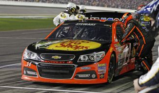 Crew members work on Tony Stewart's car during the NASCAR Daytona 500 Sprint Cup series auto race at Daytona International Speedway in Daytona Beach, Fla., Sunday, Feb. 23, 2014. (AP Photo/Terry Renna)
