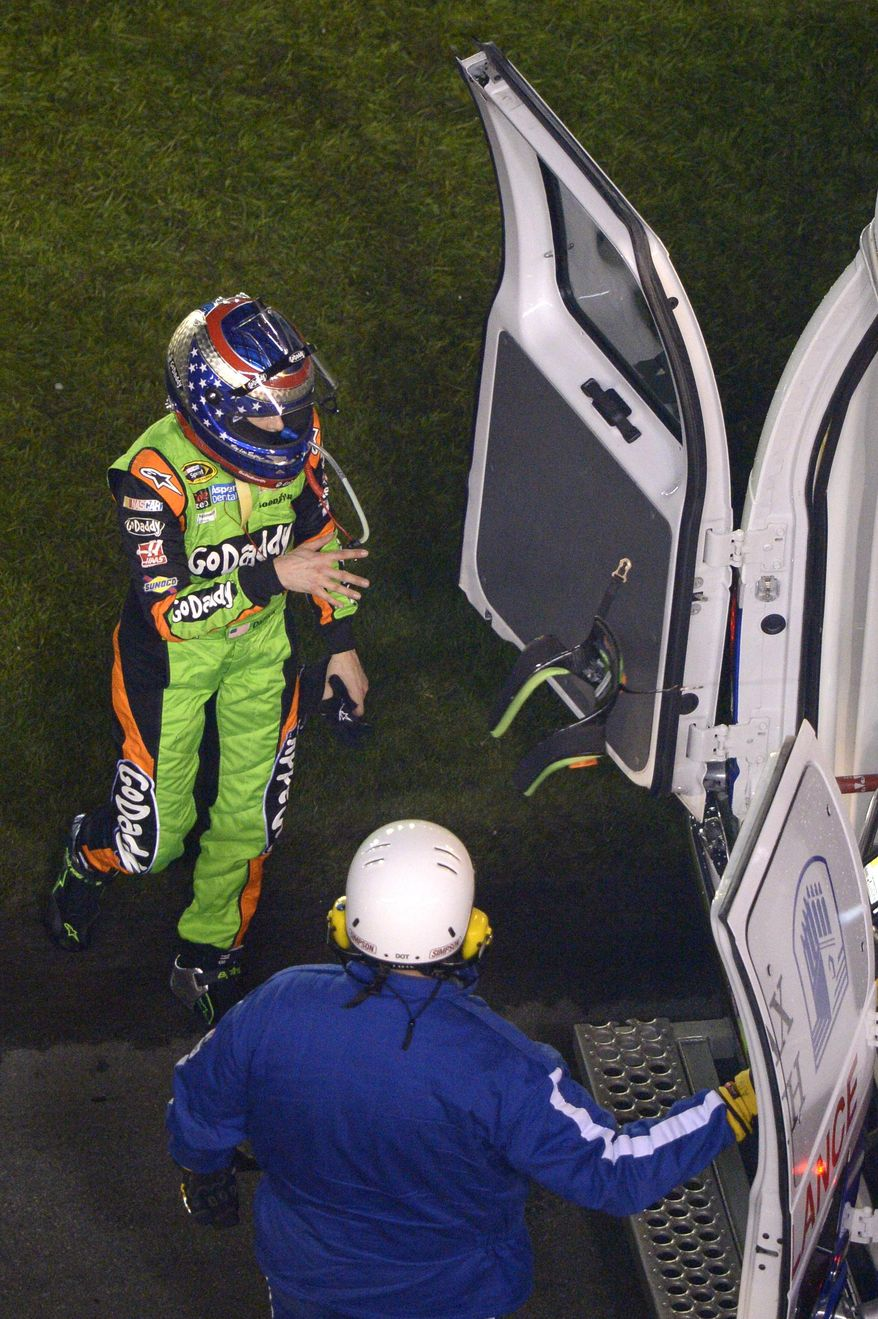 Danica Patrick, left, throws her harness into the back of an ambulance after wrecking her car during the NASCAR Daytona 500 auto race at Daytona International Speedway in Daytona Beach, Fla., Sunday, Feb. 23, 2014. (AP Photo/Phelan M. Ebenhack)