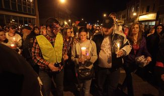 Stacey Baarfield, center, mother of Hailey Owens, and husband, Jeff, right, lead a march and vigil honoring their daughter Saturday night Feb. 22, 2014. ((AP Photo/The Springfield News-Leader, Dean Curtis)