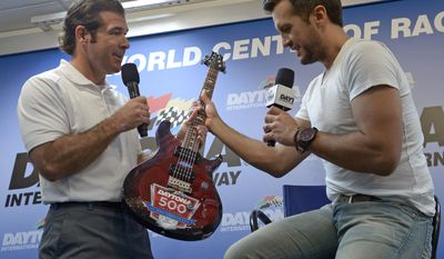 Speedway president Joie Chitwood, left, gives singer Luke Bryan, right, a guitar during a news conference before the NASCAR Daytona 500 Sprint Cup series auto race at Daytona International Speedway in Daytona Beach, Fla., Sunday, Feb. 23, 2014. (AP Photo/Phelan M. Ebenhack)