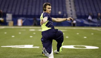 Texas A&M quarterback Johnny Manziel warms up before running the 40-yard dash at the NFL football scouting combine in Indianapolis, Sunday, Feb. 23, 2014. (AP Photo/Michael Conroy)