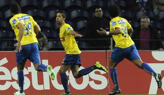 Estoril's Evandro Goebel, centre, celebrates with Bruno Lopes, both from Brazil, and Carlitos Garcia, right, after scoring a penalty goal against FC Porto in a Portuguese League soccer match at the Dragao stadium, in Porto, Portugal, Sunday, Feb. 23, 2014. Porto lost 1-0.(AP Photo/Paulo Duarte)
