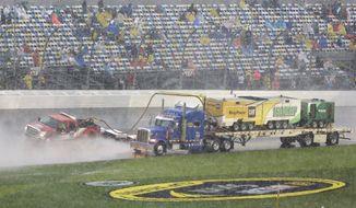 Track dryers go along the front stretch during a rain delay in the Daytona 500 NASCAR Sprint Cup Series auto race at Daytona International Speedway in Daytona Beach, Fla., Sunday, Feb. 23, 2014. (AP Photo/John Raoux)