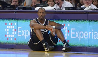 Brooklyn Nets center Jason Collins waits to come into the game during the second half of an NBA basketball game against the Los Angeles Lakers, Sunday, Feb. 23, 2014, in Los Angeles. The Nets won 108-102. (AP Photo/Mark J. Terrill)