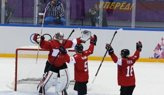 Canada goaltender Carey Price celebrates with defenseman Dan Hamhuis and forward Jonathan Toews after the men's gold medal ice hockey game against Sweden at the 2014 Winter Olympics, Sunday, Feb. 23, 2014, in Sochi, Russia. Canada won 3-0 to win the gold medal. (AP Photo/David J. Phillip )