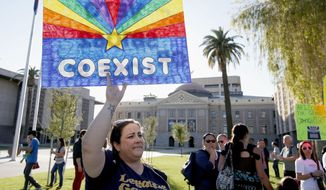 Jo Beaudry holds up a sign as she joins nearly 250 gay rights supporters protesting SB1062 at the Arizona Capitol, Friday, Feb. 21, 2014, in Phoenix.  The protesters gathered demanding Gov. Jan Brewer veto legislation that would allow business owners to refuse to serve gays by citing their religious beliefs.  The governor must sign or veto Senate Bill 1062 by the end of next week. (AP Photo/Ross D. Franklin)