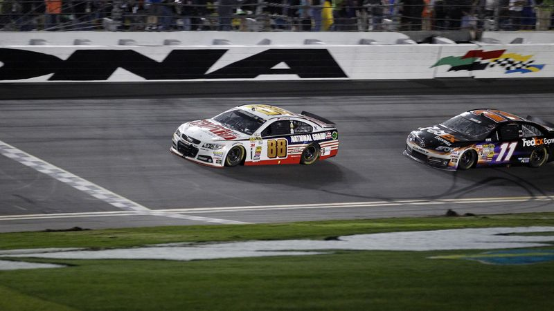 Dale Earnhardt Jr. (88) defeats Denny Hamlin (11) to the finish line to win the NASCAR Daytona 500 Sprint Cup series auto race at Daytona International Speedway in Daytona Beach, Fla., Sunday, Feb. 23, 2014. (AP Photo/Terry Renna)