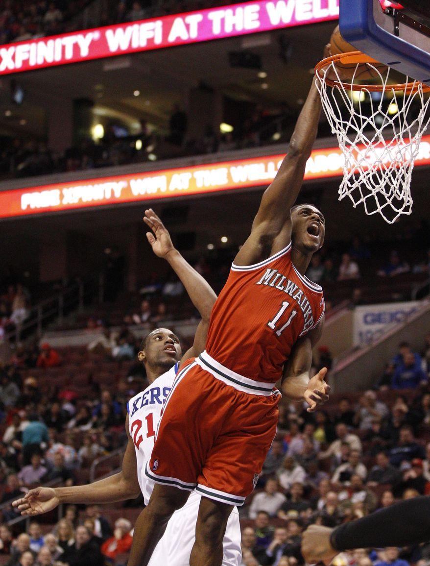 Milwaukee Bucks' Brandon Knight (11) dunks the ball past Philadelphia 76ers' Thaddeus Young, left, during the first half of an NBA basketball game, Monday, Feb. 24, 2014, in Philadelphia. (AP Photo/Chris Szagola)
