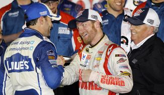 Dale Earnhardt Jr., center, celebrates in Victory Lane with teammate Jimmie Johnson, left, and team owner Rick Hendrick, right, after winning the NASCAR Daytona 500 Sprint Cup series auto race at Daytona International Speedway in Daytona Beach, Fla., Sunday, Feb. 23, 2014. (AP Photo/Terry Renna)