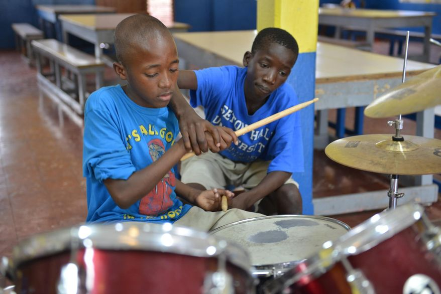 In this Feb. 17, 2014 photo, 14-year-old Brad Hylton helps classmate Omar Bird play a drum beat with the band at Alpha Boys' School, a residential vocational school in Kingston, Jamaica. The school has been a cornerstone of Jamaica's prolific musical culture for over a century, producing numerous musicians who have taken the homegrown musical genres of ska, rocksteady and reggae to the world. (AP Photo/David McFadden)