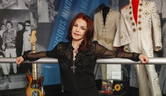"""Priscilla Presley stands in the """"60 years of Elvis"""" exhibit inside an annex at Graceland on Friday, Feb. 21, 2014, in Memphis, Tenn. The exhibit, which opens Monday, Feb. 24, 2014 features jump suits worn by Presley, an organ played in his California home, a copy of the original """"That's All Right"""" record and other miscellaneous Elvis items. (AP Photo/Lance Murphey)"""