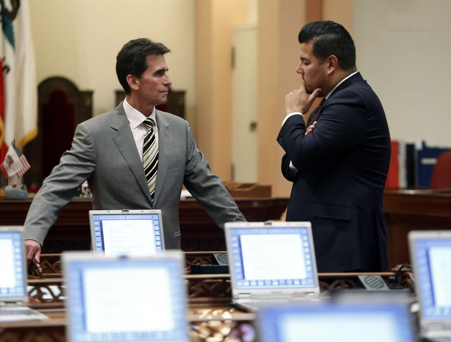 Democratic state Senators, Mark Leno, of San Francisco, left, and Ricardo Lara, D-Los Angeles, chairman of the Latino Caucus, confer at the Capitol in Sacramento, Calif., Monday Feb. 24, 2014.  After a closed door meeting, Senate Democrats said they give state Sen. Ron Calderon, D-Montebello, one week to resign or take an indefinite leave of absence. If he does not, the Senate will move to suspend him. Calderon was arraigned Monday in Los Angeles on charges that he accepted $100,000 in bribes and trips. (AP Photo/Rich Pedroncelli)