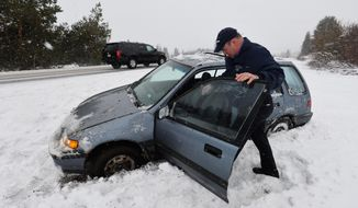 Bill Froyd of Blaine, Wash., waits for a tow truck on Interstate 5 northbound, Monday, Feb. 24, 2014, north of Ferndale, Wash., after a gust of wind spun him off the road. (AP Photo/The Bellingham Herald, Philip A. Dwyer)