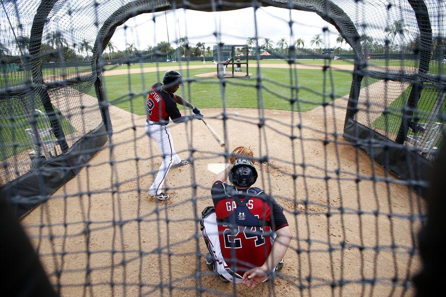 Atlanta Braves center fielder B.J. Upton (2) swings at a pitch with Evan Gattis (24) catching, during a spring training baseball workout, Monday, Feb. 24, 2014, in Kissimmee, Fla. (AP Photo/Alex Brandon)
