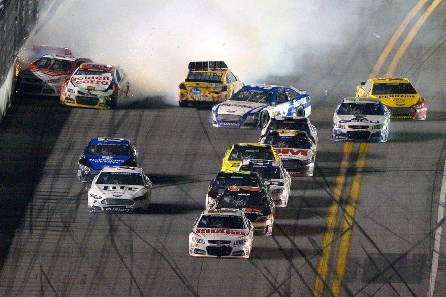 Dale Earnhardt Jr. (88) escapes a final lap wreck and leads to win the NASCAR Daytona 500 auto race at Daytona International Speedway in Daytona Beach, Fla., Sunday, Feb. 23, 2014. (AP Photo/Phelan M. Ebenhack)