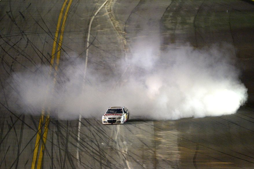 Dale Earnhardt Jr. (88) emerges from a cloud of smoke after winning the NASCAR Daytona 500 auto race at Daytona International Speedway in Daytona Beach, Fla., Sunday, Feb. 23, 2014. (AP Photo/Phelan M. Ebenhack)