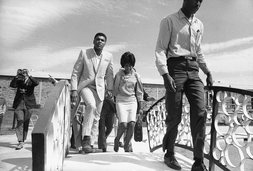 Heavyweight boxing champion Muhammad Ali (Cassius Clay), accompanies by his wife Sonji, walks across bridge at motel in nearby Auburn after arrival in Lewiston, Me on May 23, 1965.   They had motored to Auburn from his Chicopee Falls, Mass., training camp.   Ali  defends title on Tuesday in Lewiston against Sonny Liston. (AP Photo)