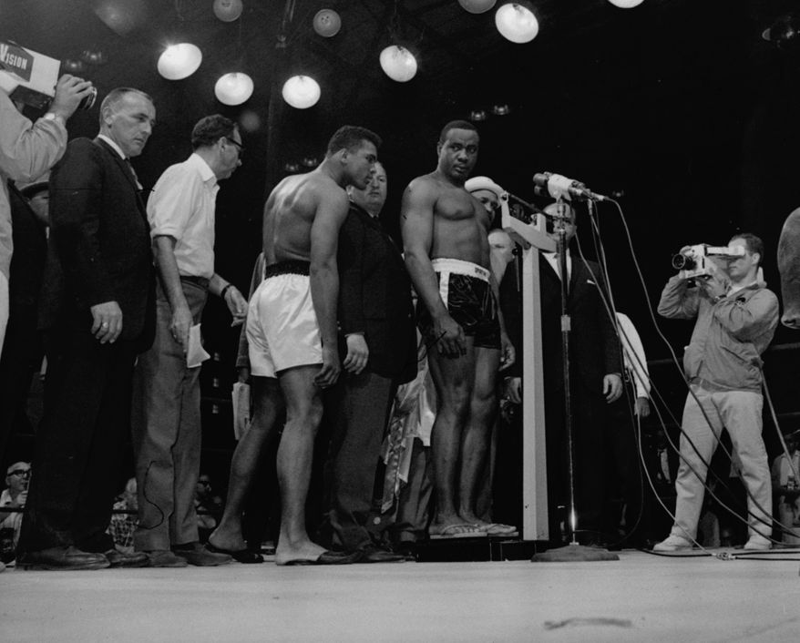 Heavyweight champion Muhammad Ali, left, is shown peering over to read scales as the weight of challenger Sonny Liston was first announced as 219 1/2, May 25, 1965, through error.  After a recheck, it was set at 215 1/4.  Ali came in at 206. (AP Photo/stf)