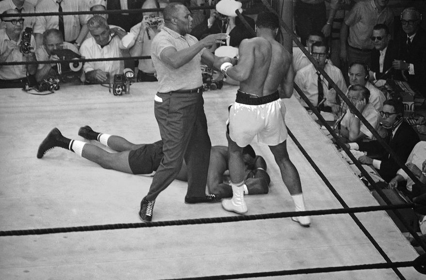 Referees Jersey Joe Walcott tries to restrain an eager Muhammad Ali (Cassius Clay)  as the heavyweight champion stood ready to resume action against a downed Sonny Liston in Lewiston, Maine on May 26, 1965 title fight.  Ali  kept his title via a one-round KO. (AP Photo)