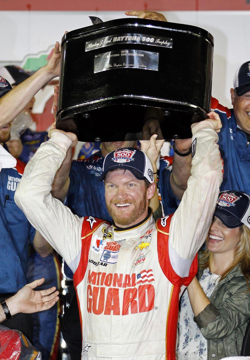 Dale Earnhardt Jr. raises the trophy in Victory Lane after winning the NASCAR Daytona 500 Sprint Cup series auto race at Daytona International Speedway in Daytona Beach, Fla., Sunday, Feb. 23, 2014. (AP Photo/Terry Renna)