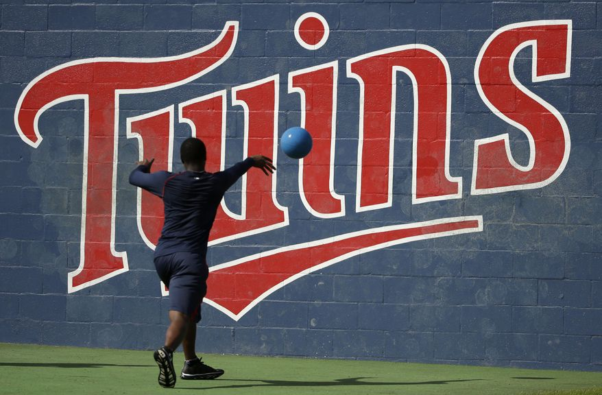 Minor league baseball player Randy Rosario works out with a ball in front of a Minnesota Twins logo at the Twins' spring  training baseball facility, Friday, Feb. 21, 2014, in Fort Myers, Fla. (AP Photo/Steven Senne)
