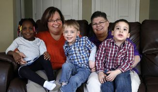 FILE- In a March 5, 2013, file photo, April DeBoer, second from left, sits with her adopted daughter Ryanne, left, 3, and Jayne Rowse, fourth from left, and her adopted sons Jacob, 3, middle, and Nolan, 4, right, at their home in Hazel Park, Mich. On Tuesday, Feb. 25, 2014, U.S. District Judge Bernard Friedman is scheduled to open a trial on the women's challenge to Michigan's ban on gay marriage and joint adoptions by same-sex couples. (AP Photo/Paul Sancya, File)