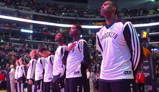 Brooklyn Nets center Jason Collins, right, listens to the national anthem prior to an NBA basketball game against the Los Angeles Lakers, Sunday, Feb. 23, 2014, in Los Angeles. Collins signed a 10-day contract with the Nets earlier Sunday. The 35-year-old center revealed at the end of last season he is gay, but he was a free agent and had remained unsigned. (AP Photo/Mark J. Terrill)