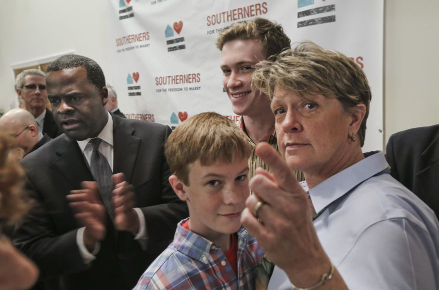 """Atlanta Mayor Kasim Reed, left, applauds at the conclusion of an event, Monday, Feb. 24, 20414, in Atlanta, with Sam Ellis, 12, left center, and his brother John, 15, right center, mother Linda Ellis, who along with her partner, Lesley Brogan (not pictured), participated. The Ellis family was included in the event. Reed was among those kicking off the """"Southerners for the Freedom to Marry"""" campaign, saying he believes gay marriage supporters are on the """"right side of history."""" (AP Photo/Atlanta Journal-Constitution, John Spink) MARIETTA DAILY OUT; GWINNETT DAILY POST OUT; LOCAL TV OUT; WXIA-TV OUT; WGCL-TV OUT."""