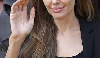 This photo taken Feb. 24, 2014 shows actress Angelina Jolie waving as she leaves the government palace in Beirut, Lebanon. For women who carry a notorious cancer gene, surgery to remove healthy ovaries is one of the most protective steps they can take. New research suggests some may benefit most from having the operation as young as 35. Women who inherit either of two faulty BRCA genes are at much higher risk of developing breast and ovarian cancer than other women, and at younger ages. Jolie generated headlines last year when she had her healthy breasts removed to reduce her cancer risk. (AP Photo/Hussein Malla)